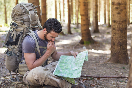 vacation map: Beard Man with Backpack and map searching directions in wilderness area