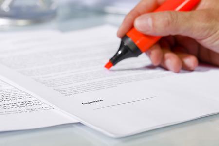 revisando documentos: Primer plano de la mano del hombre con rotulador sobre el documento, verificar el contenido antes de firmar. Concepto de negocio y el acuerdo