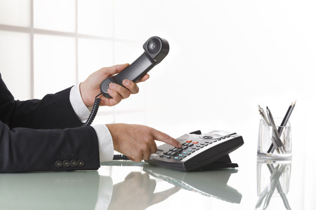 Businessman with dark gray suit dialing the number on a black landline telephone.  Closeup of his hand and the telephone on an office table whit pen. Concept of business and communication.