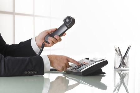 ejecutivos: Hombre de negocios con traje gris oscuro de marcar el número de un teléfono fijo negro. Primer plano de la mano y el teléfono en una mesa de la oficina de la pizca de la pluma. Concepto de negocios y la comunicación.
