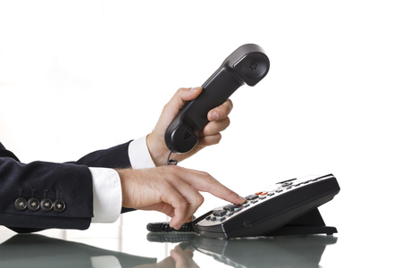 Businessman with dark gray suit dialing the number on a black landline telephone.  Closeup of his hand and the telephone on a white background. Concept of business and communication. Standard-Bild