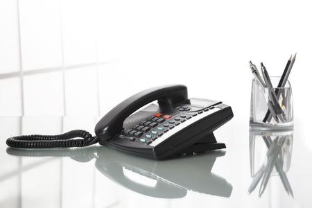 personas hablando: Cierre de tel�fono fijo negro sobre un escritorio de oficina con el fondo blanco