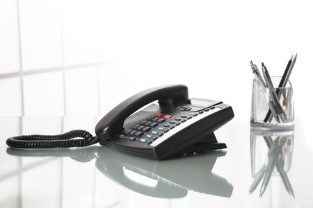 Close up of black landline phone on an office desk with white background