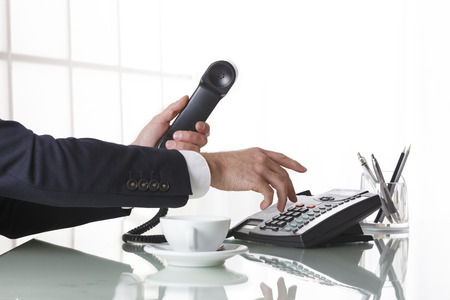 man in suit: Hand of a businessman with dark gray suit holding the receiver of a black landline telephone while dialing, with a cup of coffee on the office table. Concept of business and communcation. Stock Photo