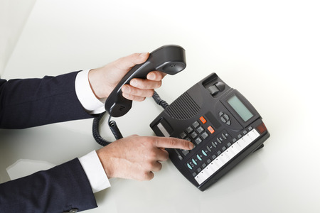 Top view of businessman with dark gray suit dialing the number on a black landline telephone.  Closeup of his hand and the telephone. Concept of business and communication.