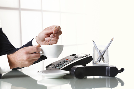 businessman waiting call: Close up of businessman hand with dark gray suit stirring a cup of coffee on the office desk with a black landline telephone. Concept of work break. Stock Photo
