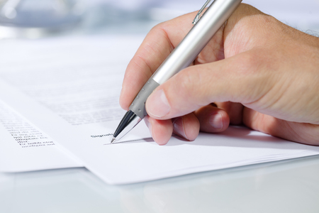 businessman signing documents: Close-up shot of hand signing a document with a silver pen. Concept of business and agreement
