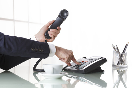 phone receiver: Hand of a businessman with dark gray suit holding the receiver of a black landline telephone while firmly pressing a button on telephone, with a cup of coffee and pens on a white office table. Concept of business and communcation. Stock Photo