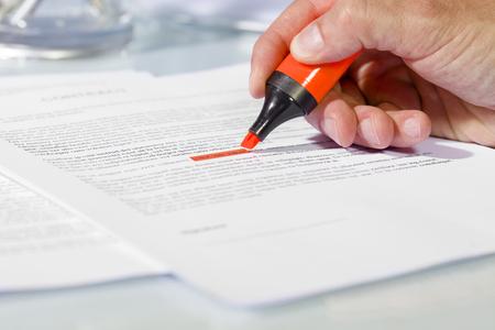 ドキュメントは、署名する前に内容を確認の上の蛍光ペンで人間の手のクローズ アップ。ビジネスと契約の概念 写真素材