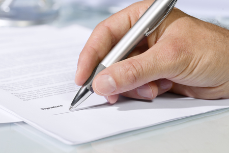 Close-up shot of hand signing a document with a silver pen. Concept of business and agreement