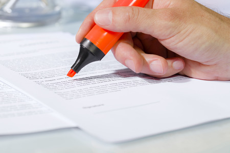 undersign: Close-up of man hand with highlighter over document, checking the content before signing. Concept of business and agreement