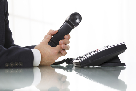 suspense: Businessman with dark gray suit holding the receiver of a black landline telephone. Close up of his arms and the telephone on a white background. Concept of business and communication.