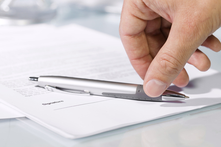 Close-up of a hand taking a silver pen to sign document on a desk. Concept of business and agreement
