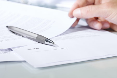 undersign: Close-up shot of a silver pen on a desk with documents and hand. Concept of business and agreement