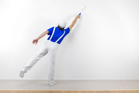 pintor: Vista trasera del pintor en ropa de trabajo blanca, azul de la camiseta y gorra con paintroller pintura de una pared blanca.