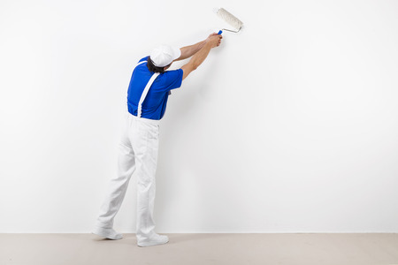 paintroller: Rear view of painter in white workwear, blue t-shirt and cap with paintroller painting a white wall Stock Photo