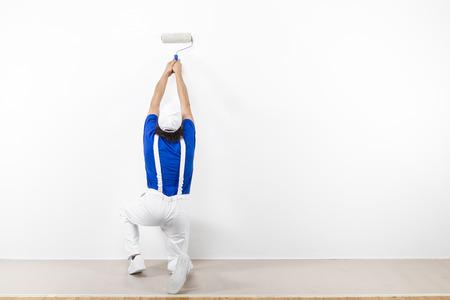 en cuclillas: Vista trasera de cuclillas pintor en ropa de trabajo blanca, camiseta azul y una gorra con paintroller pintura de una pared blanca.