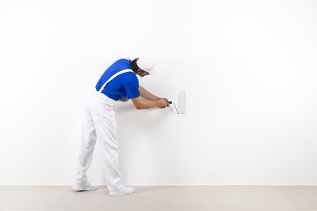 painter: Rear view of painter in white workwear, blue t-shirt and cap with paintroller painting a white wall.