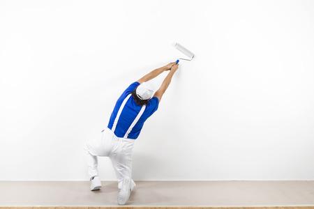 cuclillas: Vista trasera de cuclillas pintor en ropa de trabajo blanca, camiseta azul y una gorra con paintroller pintura de una pared blanca.