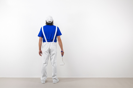 paintroller: Rear view of painter in white workwear, blue t-shirt and cap with paintroller looking at a white wall