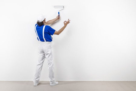 paintroller: Rear view of painter in white workwear, blue t-shirt and cap with paintroller painting a white wall and doing ok. Stock Photo