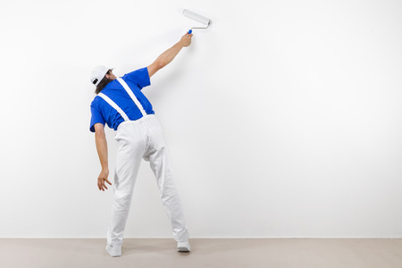 Rear view of painter in white workwear, blue t-shirt and cap with paintroller painting a white wall.