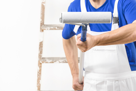 Headless close up shot of painter man aiming at you with paint roller. Stock Photo