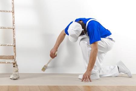HOMBRE PINTANDO: Pintor en el trabajo hombre con el cepillo de la pintura de una pared blanca.