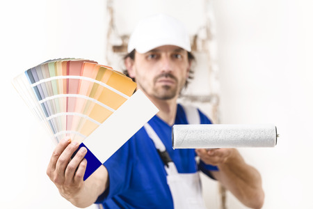 paintroller: Close up shot of painter man with paintroller showing a color palette