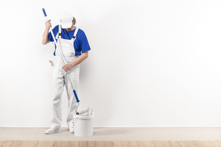 white color worker: Painter man at work takes the color with paint roller from the bucket. With copy space Stock Photo