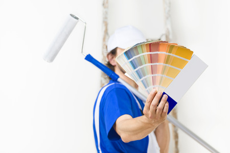Close up shot of painter man with paintroller showing a color palette