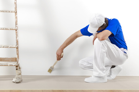 painter and decorator: Painter man at work with brush painting a white wall.
