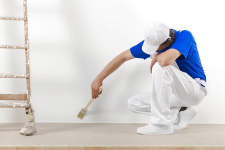 pintor: Pintor en el trabajo hombre con el cepillo de la pintura de una pared blanca.