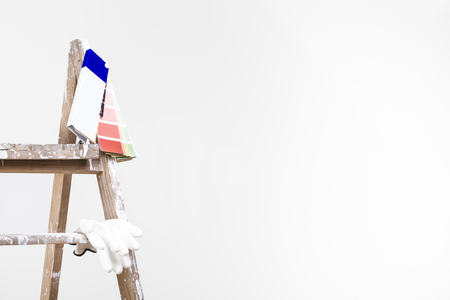 Painter wall concept: close up shot of used vintage ladder with color palette and gloves in an empty room