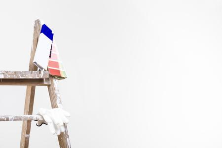 Het concept van de schildersmuur: sluit omhoog geschoten van gebruikte uitstekende ladder met kleurenpalet en handschoenen in een lege ruimte Stockfoto