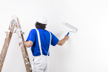 paintroller: Painter man at work climbing a vintage wooden ladder and painting with paintroller Stock Photo