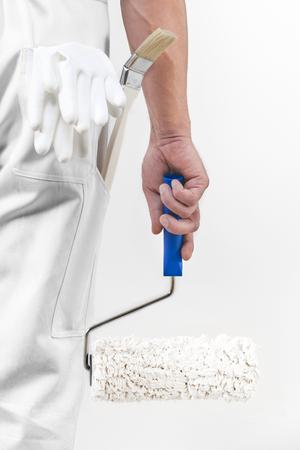pintor de casas: Vista trasera de un pintor con el rodillo de pintura. De cerca. Foto de archivo