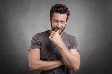formal portrait: Handsome young man wearing grey t-shirt winking against grey background
