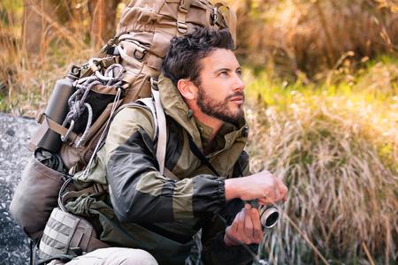 cuclillas: Retrato hermoso Hicker cuclillas con c�mara de la vendimia, que est� mirando hacia el lado. Hombre joven en el bosque. Estilo de vida activo, el turismo de naturaleza. Foto de archivo