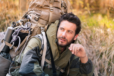 cuclillas: Retrato hermoso cuclillas hicker, �l est� mirando a un lado. Hombre joven en el bosque. estilo de vida activo, el turismo en la naturaleza.