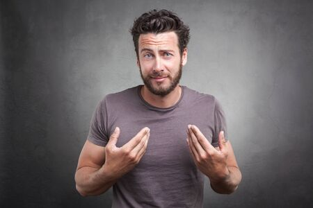 frontal portrait: Frontal portrait of adult man getting surprised unexpected attention from people, asking you talking to, I mean pointing finger at himself isolated on gray background. Facial expression body language
