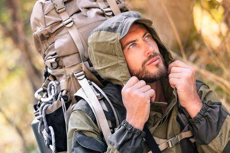 beau mec: Beau jeune homme portrait, il est à la recherche sur le côté. guy capuche randonnée dans la forêt. Mode de vie actif, le tourisme dans la nature.