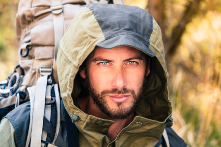 Handsome young man portrait, he is looking at camera. Hooded guy hiking in the forest. Active lifestyle, tourism in nature. Stock Photo