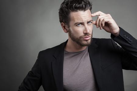 стиль жизни: Красивый молодой человек, носить серый костюм мышление. Он смотрит на камеру сером фоне. Фото со стока