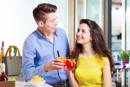 flirting: Teenager couple smiling and toasting with cocktail in the coffee bar