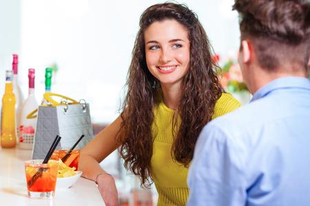 conversaciones: Selectivo se centran en una muchacha joven y sonriente hablando con el chico frente a ella, con un cóctel en el bar counter Foto de archivo