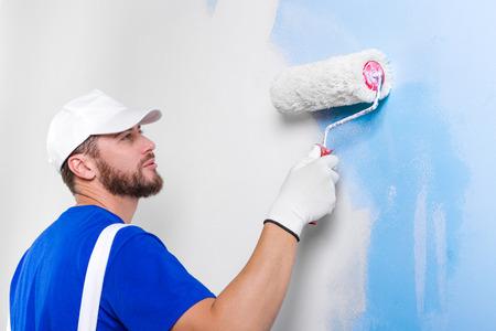 pintor de casas: Retrato del pintor joven y guapo en un peto blanco, camiseta azul, gorra y guantes de pintura de una pared con el rodillo de pintura.