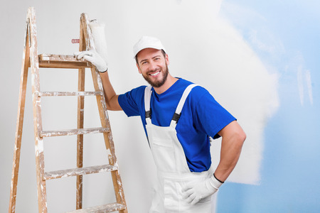 Portrait of handsome young smiling painter in white dungarees, blue t-shirt, cap and gloves leaning on a vintage ladder with paint roller, looking at camera
