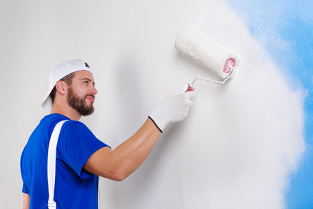 dungarees: Portrait of handsome young painter in white dungarees; blue t-shirt; cap and gloves painting a wall with paint roller. Stock Photo