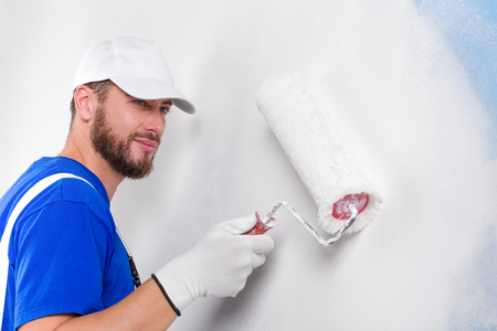 dungarees: Portrait of handsome young painter in white dungarees, blue t-shirt, cap and gloves painting a wall with paint roller. Stock Photo